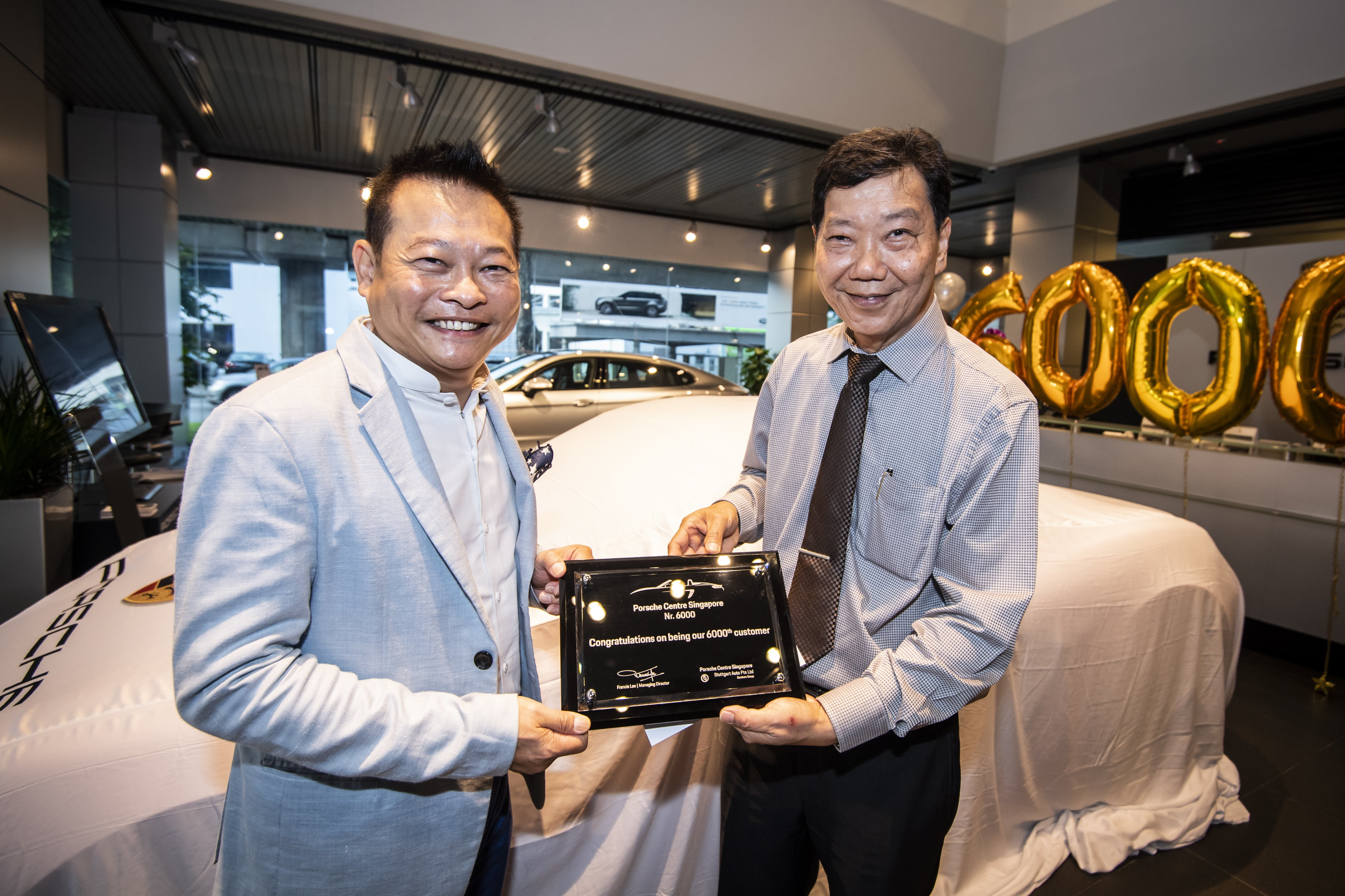 Mr Francis Lee, Managing Director of Stuttgart Auto (right) presenting a commemorative plaque to the new owner of the 6,000th Porsche car in Singapore, Mr Joe Goh