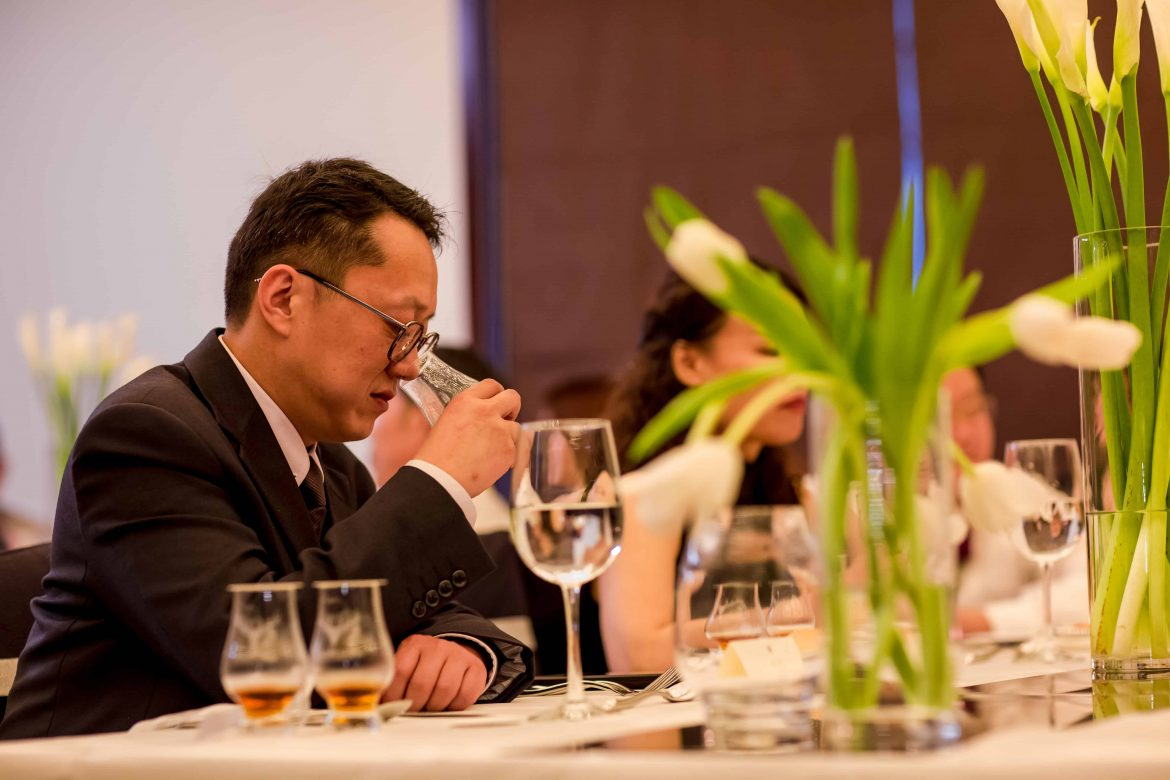 A Rolls-Royce guest enjoying a glass of whisky at the whisky tasting session