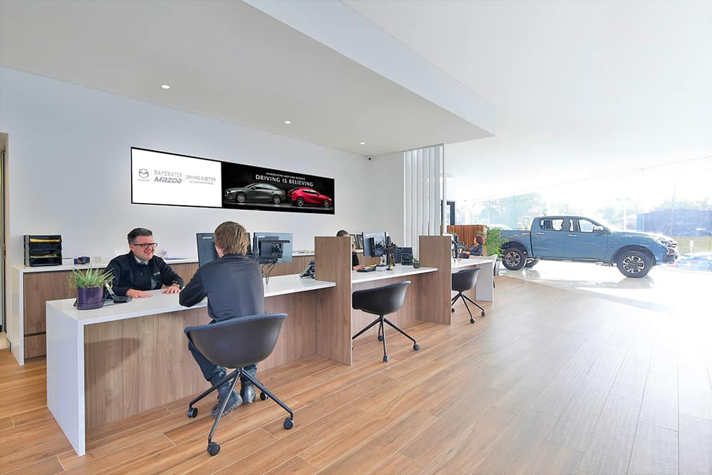 A Mazda Sales Consultant engaging with a customer in the spacious and luxurious interior of the new Bayswater Mazda showroom